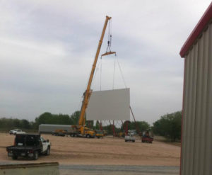 A crane lifts a drive-in screen into place during construction