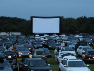 Rows of cars lined up in front of an inflatable screen