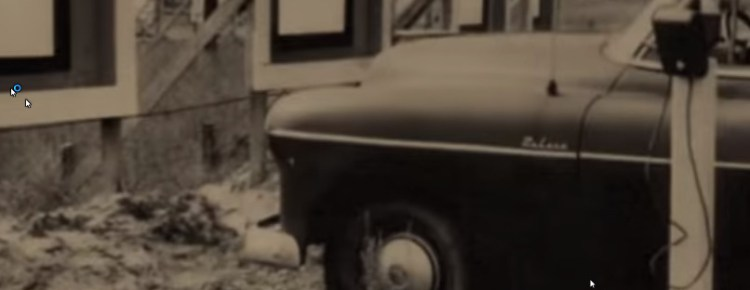 Old car with a drive-in speaker sitting directly in front of a small screen