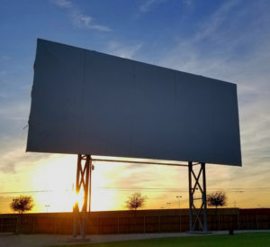 Coyote Drive-In screen tower silhouetted at sunset