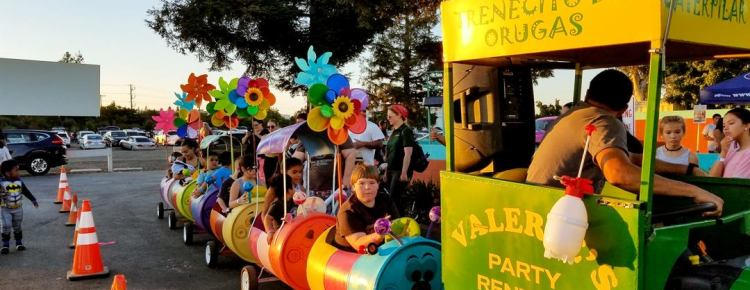 Colorful tractor-train carries kids through the parking lot