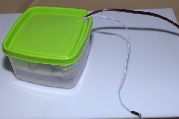 O tupperware já fechado, com o cabo do sensor de luminosidade e do casquilho no exterior