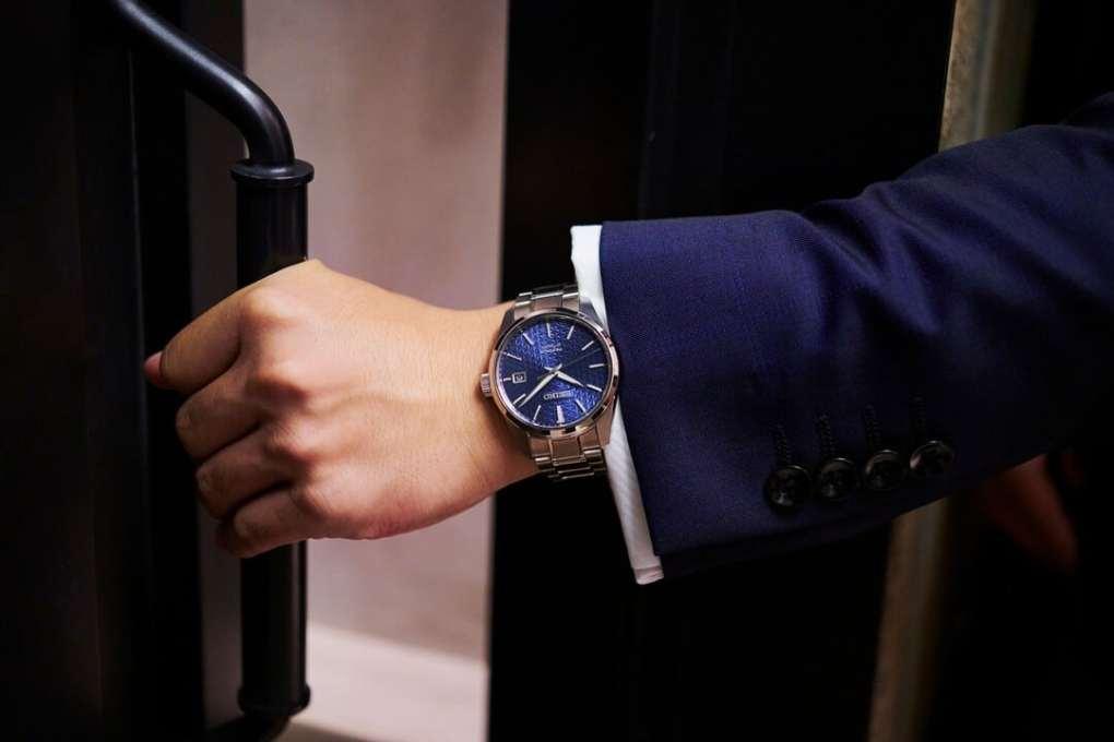 Mann i blå dress med blå klokke