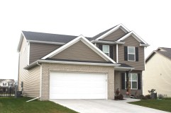 2 story house with dark brown siding, white trim, white garage door, tan brick and black roof. black raised panel shutters