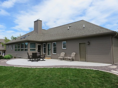 Ranch house with back patio sitting area and tan siding