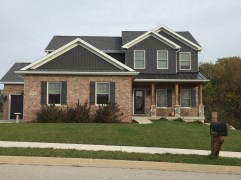two story house with dark grey siding, red/tan brick, cedar posts and dark grey metal roof