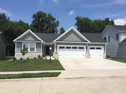 smaller ranch house with grey siding, grey shakes, white trim, white carriage style garage door with plain glass inserts, Black roofing and tan bricks