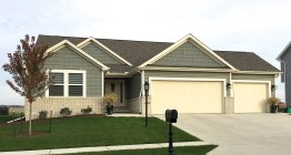 one story green home with tan brick and cream trim