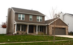 two story brown home with brown brick and brown garage door and white trim