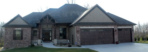Large ranch home with wooden gable entrance and wooden garage doors