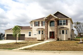 2 story house with tall brick arched columns, light tan siding, dark brown shakes, brown roof