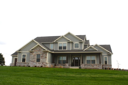 grand ranch style home with green siding, cream trim and stone accents