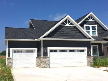 home with grey siding and dark grey shakes with black roof carriage style garage door and stone knee wall