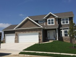 house with brown siding and brown shakes with brown multi colored brick, white trim, white recessed panel garage door