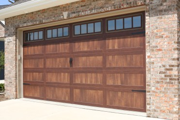 wooden garage door with hardware and windows with vertical slates