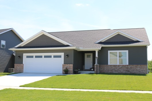 Misty Shadow dark siding and match shakes pops wth the white wide trim and garage door in Mahomet IL