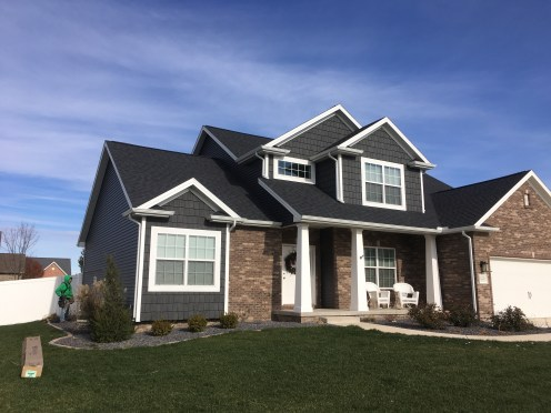 dark grey siding and shakes with white trim and dark roof, brown brick and white garage door, craftsman style columns