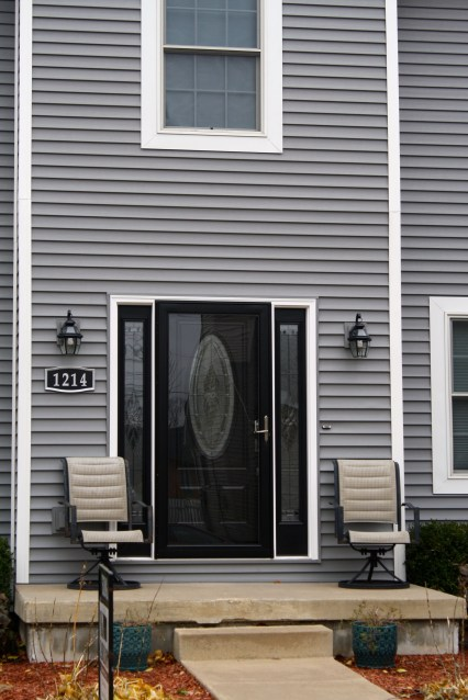 Black door with oval glass and two full length sidelights in grey home