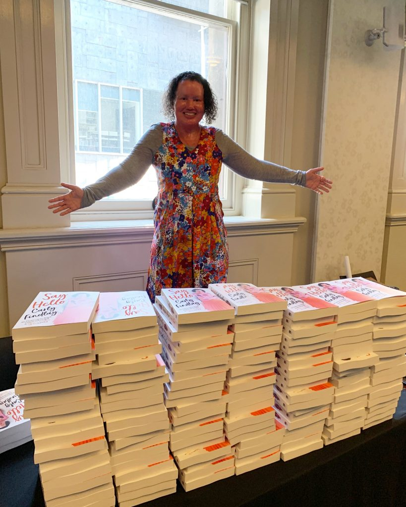 Woman with red face and short dark curly hair, standing over a pile of books. Her arms are outstretched. She's smiling.