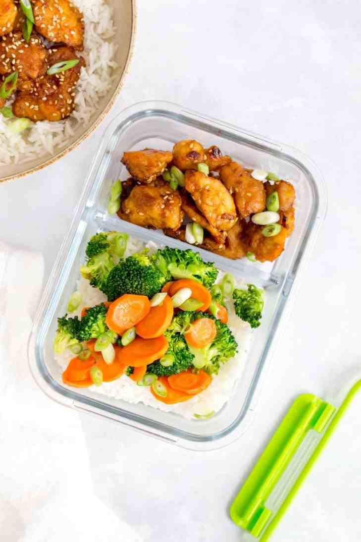 Bento box of sesame chicken in a glass meal prep container with rice and vegetables.