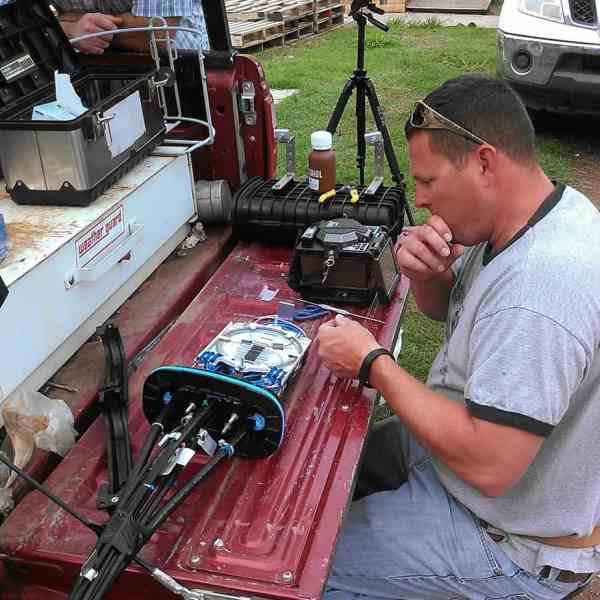 Matt Smith and Travis Ridgeway are resplicing a fiber optic line for the First Baptist Church in Carnegie