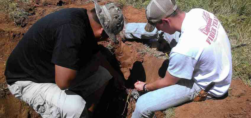Picture of two technicians repairing a cut phone cable