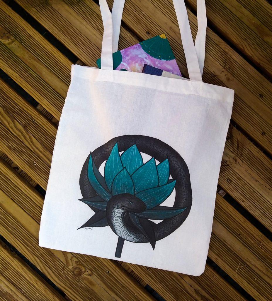 Photographie d'un sac en coton avec une illustration d'un serpent noir protégeant une fleur bleue