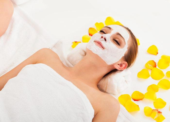 Women with a face mask, laying down with yellow petals around her in a towel