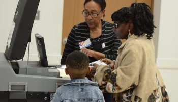 Dorothy Taylor, right, places her 2020 primary election ballot in the scanner while her grandson Julian Taylor and poll worker Georgia Everett looks on at the Edgecombe County Administrative Building polling place in Tarboro on March 3, 2020. Calvin Adkins / Carolina Public Press