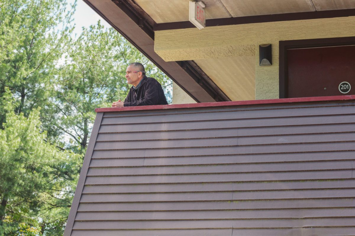 José Valadez looks over the balcony at the Red Roof Inn in Asheville on Tuesday. Valadez is a client of Homeward Bound, which began housing otherwise homeless clients at the motel during the coronavirus pandemic this week. Jacob Biba / Carolina Public Press