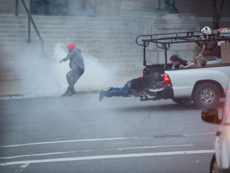 As police release tear gas to disperse protesters in downtown Asheville Wednesday night, one man dives into the back of a moving truck and another staggers in a cloud of the gas. Colby Rabon / Carolina Public Press