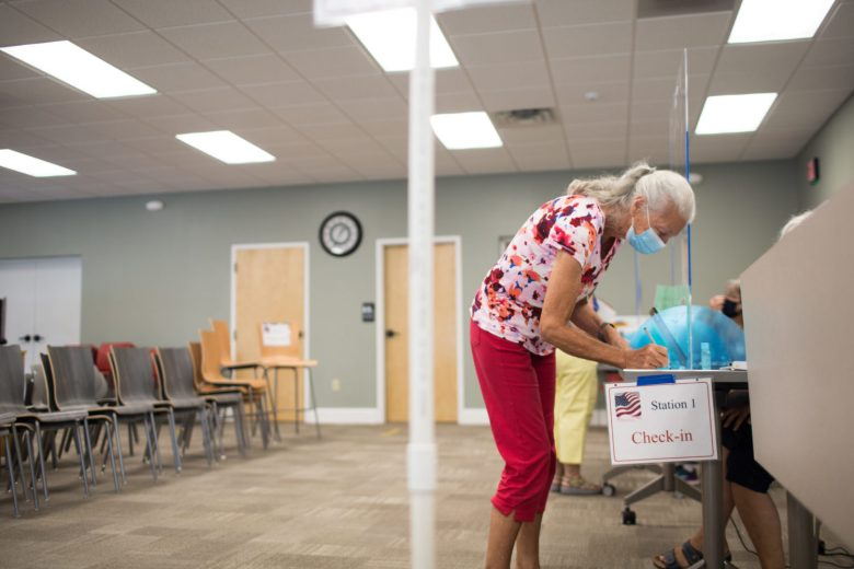 Jenefer McArthur wears a masks and talks with election officials through a clear partition as she signs in to cast her vote Tuesday, June 23, 2020, at the Enka/Candler library in Buncombe County. Colby Rabon / Carolina Public Press