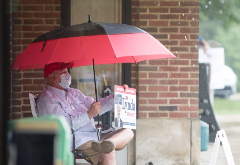 Jim Meadows wears and mask and carries an umbrella as he braves thunderstorms and the COVID-19 pandemic to campaign for Lynda Bennett outside the Enka/Candler library in Buncombe County on Tuesday. Bennett ultimately lost the second primary contest to Madison Cawthorn. Colby Rabon / Carolina Public Press