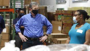 Gov. Roy Cooper talks with volunteer Anjelica Jackson Thursday while touring the Raleigh branch of the Food Bank of Central & Eastern North Carolina. Pool photo: Ethan Hyman/News and Observer