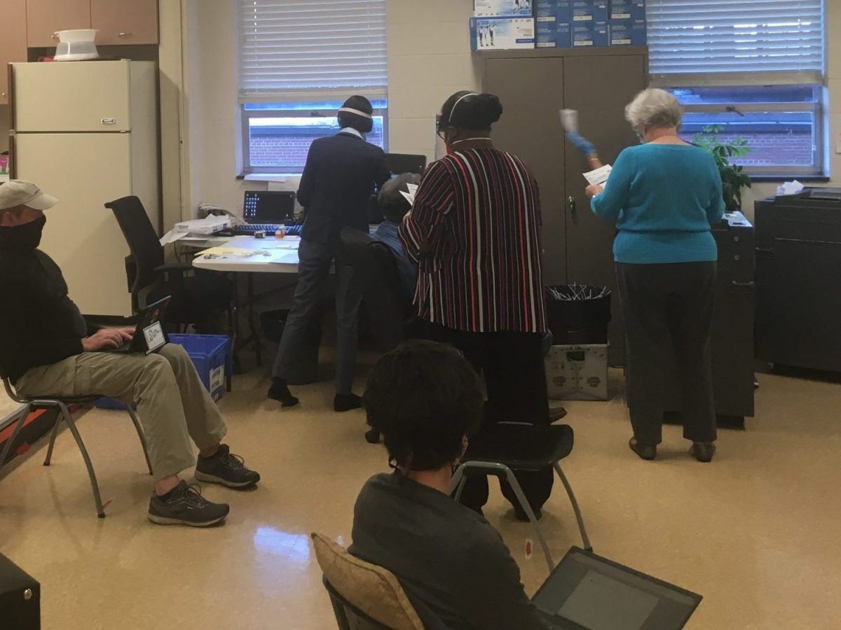 Election watchers from political parties observe Granville County Board of Elections members scan accepted absentee-by-mail ballots on Oct. 13, 2020, in Oxford. Jordan Wilkie / Carolina Public Press