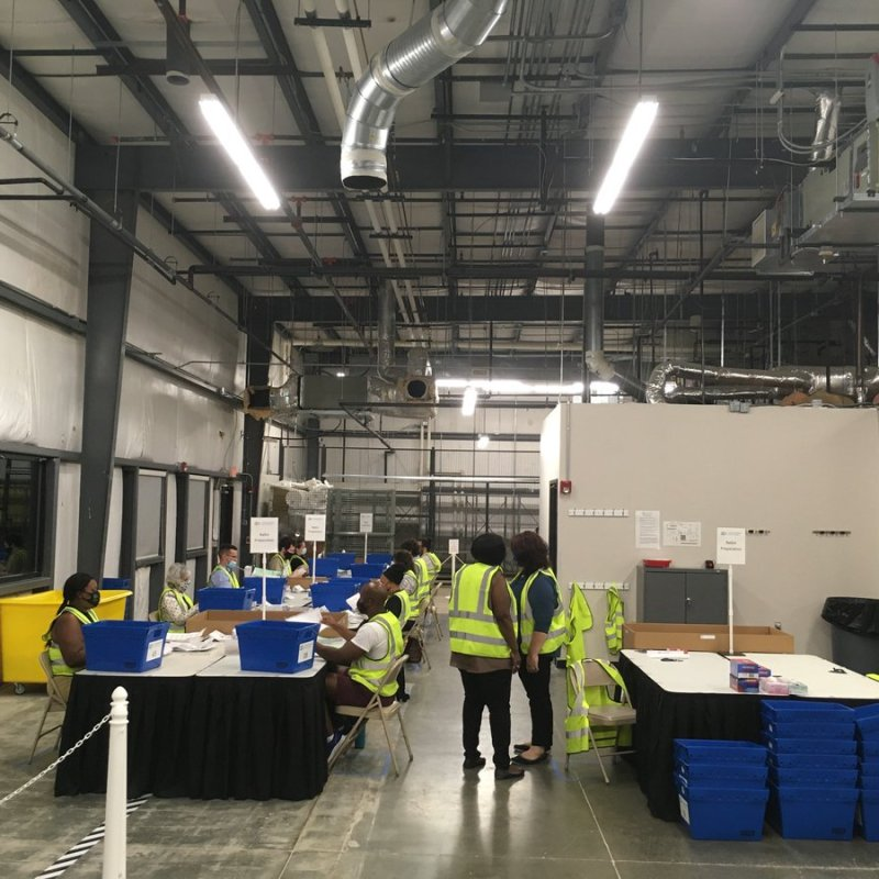 Durham County Board of Elections staff process absentee ballots at the agency's warehouse on Sept. 29, 2020. Each blue bin holds ballots from a different precinct. The workers are removing ballots from absentee-by-mail envelopes and flatten them, to be scanned in batches later on. Jordan Wilkie / Carolina Public Press