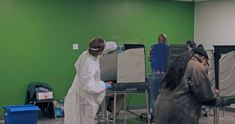 A poll worker sanitizes a voting station.