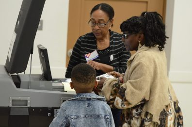Dorothy Taylor, right, places her 2020 primary election ballot in the scanner while her grandson Julian Taylor and poll worker Georgia Everett looks on at the Edgecombe County Administrative Building polling place in Tarboro on March 3, 2020. (Calvin Adkins / Carolina Public Press)