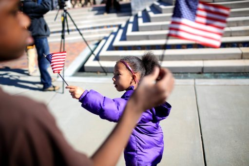 Promise Moseby, 4, waves a flag in the midst of the Martin Luther King Jr. Day events organized by the Martin Luther King Jr. Association of Asheville & Buncombe County. (Colby Rabon/Carolina Public Press)