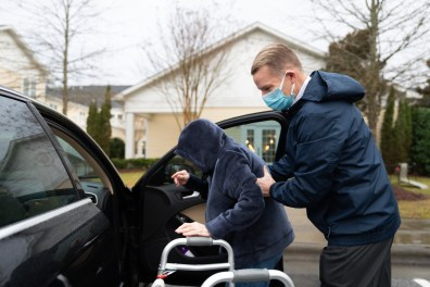 """Phil Wells helps his mother Rosalee Wells get to his car to attend a dentist appointment and get breakfast biscuits. Rosalee is a resident at Cadence Senior Living in Wake Forest, North Carolina which closed to indoor visitation more than a year ago. """"It's been a long time since I've been able to help you down the curb, huh?"""" Phil asked his mom. (Alicia Carter / Carolina Public Press)"""