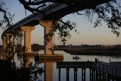 The sun sets on fishers on the intercoastal waterways of Sunset Beach, North Carolina on March 23, 2019. Bridges connect the mainland to several islands created by the intercoastal waterways where communities lie between the smaller bodies of water and the Atlantic Ocean. [Melissa Sue Gerrits/For Carolina Public Press]