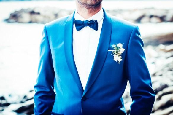 Veste bleue du marié avec noeud papillon et fleurs