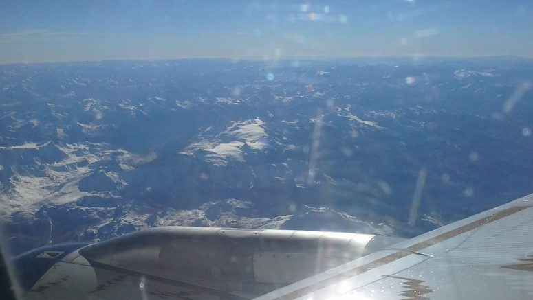 view of sky and mountains through plane window