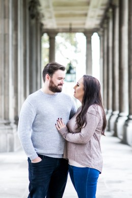 Engaged couple naturally posing amongst the colonnades at the Old Royal Navy College in Greenwich