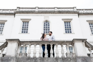 Engaged couple looking at each other at the top of the stairs in front of Queen's House in Greenwich