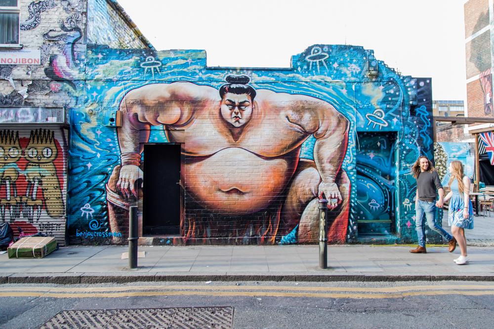 Couple walking past sumo wrestler street art in Shoreditch
