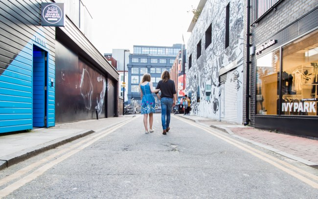 Couple walking down a Shoreditch street with graffiti