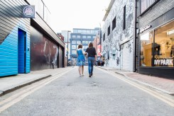 Couple walking down a Shoreditch street with graffiti