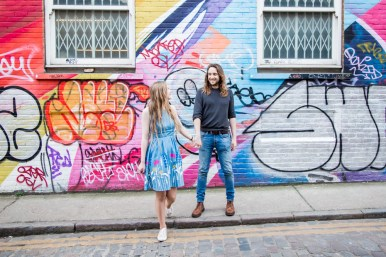 Couple holding hands against colourful wall with street art