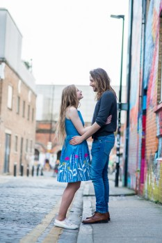 Couples shoot on cobbled street with graffiti in Shoreditch